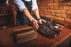 Shoemaker holding a pair of brand new shoes Stock Photo