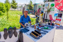 Shoemaker at the market, Uzbekistan. MARGILAN, UZBEKISTAN - AUGUST 20: Shoemaker with basic tools to repair and clean the shoes at the market. August 2016 Royalty Free Stock Photography