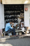 Shoemaker mending shoes. Mumbai, India. Shoemaker mending shoes in the street of the city of Mumbai. Next to the shoemaker is a client looking shoes royalty free stock photo