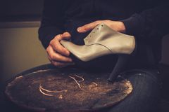 Shoemaker performs shoes in studio craft. Stock Photo