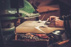 Shoemaker performs shoes in studio craft. Royalty Free Stock Image
