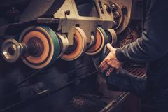 Shoemaker performs shoes in studio craft grinder machine. Stock Image