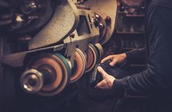 Shoemaker performs shoes in studio craft grinder machine. Royalty Free Stock Image