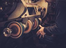 Shoemaker performs shoes in studio craft grinder machine. Shoemaker performs shoes in the studio craft grinder machine royalty free stock photography