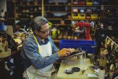 Shoemaker polishing a shoe. In workshop stock photography