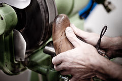 Shoemaker polishing sole of shoe. Shoemaker polishing boot-tree on the emery wheel Stock Images