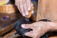 Shoemaker puts shoe polish. The shoemaker puts shoe polish Royalty Free Stock Photos
