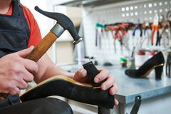 Shoemaker repair female spike shoe. Hammering tip on heel. Shoemaker and repair service. worker repair female shoe. Hammering tip on spike heel for woman Stock Images