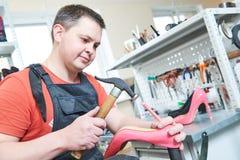 Shoemaker repair female spike shoe. Hammering tip on heel. Shoemaker and repair service. worker repair female shoe. Hammering tip on spike heel for woman Stock Photo