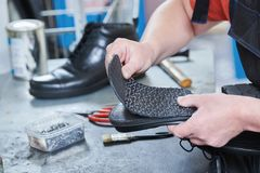 Shoemaker repair shoe. Glueing the sole for male footwear. In workshop Stock Photos