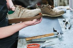 Shoemaker repair shoe. Glueing the sole for male footwear. In workshop Stock Image