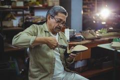 Shoemaker repairing a high heel. In workshop Stock Photos