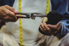Shoemaker repairing a high heel. In workshop Stock Photo