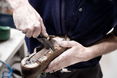 Shoemaker is repairing leather shoe. Royalty Free Stock Images
