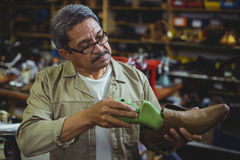 Shoemaker repairing a shoe sole. In workshop Stock Image