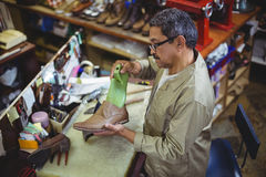 Shoemaker repairing a shoe sole. In workshop Stock Photos