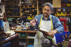 Shoemaker repairing a shoe. In workshop Stock Images