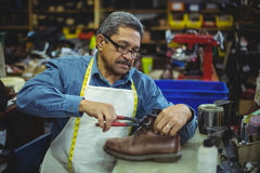 Shoemaker repairing a shoe. In workshop Stock Photography
