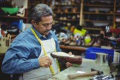 Shoemaker repairing a shoe. In workshop Stock Photos