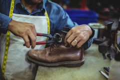 Shoemaker repairing a shoe. In workshop Royalty Free Stock Photos