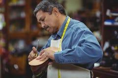 Shoemaker repairing a shoe. In workshop Stock Photo