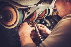 Shoemaker repairs shoes in studio craft grinder machine. Royalty Free Stock Image