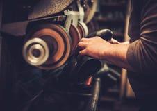 Shoemaker repairs shoes in studio craft grinder machine. Stock Photography