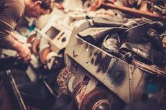 Shoemaker repairs shoes in studio craft grinder machine. Stock Photos