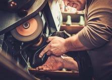 Shoemaker repairs shoes in studio craft grinder machine. Stock Images