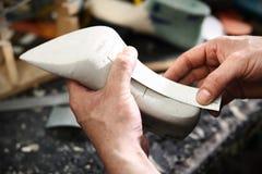 Shoemaker's workshop, append heels. Shoemaker makes chisel holes in the skin grain Royalty Free Stock Images