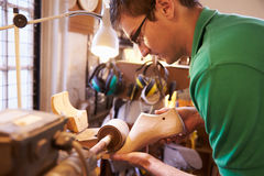 Shoemaker sanding shoe lasts in a workshop stock images