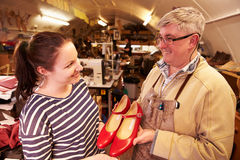 Shoemaker showing his finished work to a client Royalty Free Stock Image