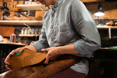 Shoemaker sitting in workshop making shoes. Cropped photo of shoemaker sitting in workshop making shoes Royalty Free Stock Photos