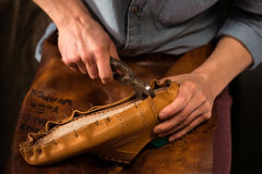 Shoemaker sitting in workshop making shoes. Cropped photo of shoemaker sitting in workshop making shoes royalty free stock photo