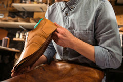 Shoemaker sitting in workshop making shoes Royalty Free Stock Photo