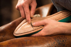 Shoemaker sitting in workshop making shoes. Cropped picture of shoemaker sitting in workshop making shoes royalty free stock photos
