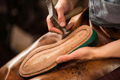 Shoemaker sitting in workshop making shoes. Cropped picture of shoemaker sitting in workshop making shoes stock photo