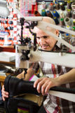 Shoemaker stitching footwear on machine Royalty Free Stock Photography