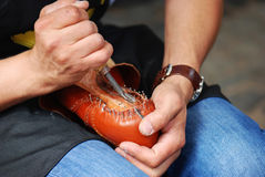 Shoemaker during work. Shoemaker manufacture a new pair of shoes by hand Royalty Free Stock Images
