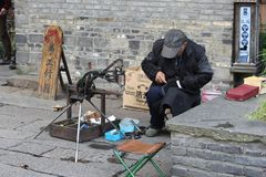 Shoemaker at work in the water town Wuzhen, China. Shoemaker is at work and repairing shoes in the water town Wuzhen (Unesco), China stock photos