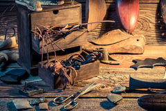 Shoemaker workplace with shoes, laces and tools Royalty Free Stock Image