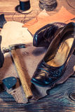 Shoemaker workplace with tools, shoes and leather Royalty Free Stock Image