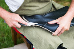 Shoemaker works on a leather high boot with his kn Royalty Free Stock Images