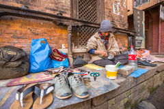 Shoemaker works on the street. The caste system is still intact today but the rules are not as rigid as they were in the past. BHAKTAPUR, NEPAL - CIRCA DEC Royalty Free Stock Photo