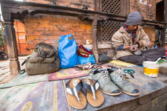 Shoemaker works on the street. The caste system is still intact today but the rules are not as rigid as they were in the past. BHAKTAPUR, NEPAL - CIRCA DEC Stock Image
