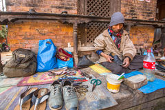 Shoemaker works on the street. The caste system is still intact today but the rules are not as rigid as they were in the past. BHAKTAPUR, NEPAL - CIRCA DEC Stock Photo