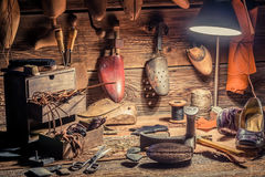 Shoemaker workshop with brush and shoes. On old wooden table royalty free stock images