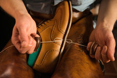 Shoemaker in workshop making shoes. Cropped image of young shoemaker in workshop making shoes Royalty Free Stock Photo