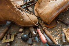 Shoemaker workshop. Old shoemaker tools with handmade shoes on workshop bench stock photos