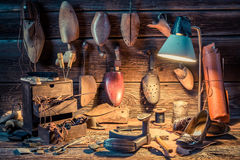 Shoemaker workshop with tools, shoes and laces Stock Photo